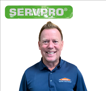 male employee standing under green SERVPRO sign